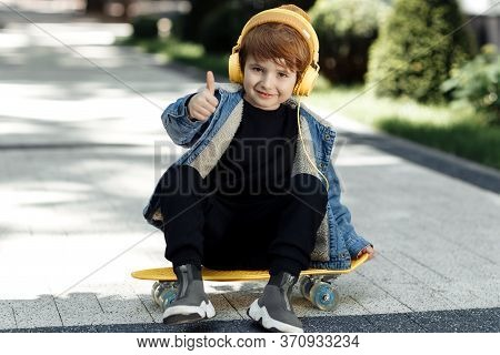 Photo Of Happy Little Boy Sitting On The Skateboard Or Pennyboard Shoy Thumb Up In Street.
