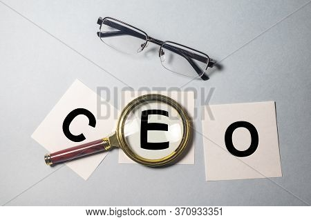 Magnifying Glass On Word Acronym Ceo On White Paper Notes With Glasses On Blue Grey Background. Ceo
