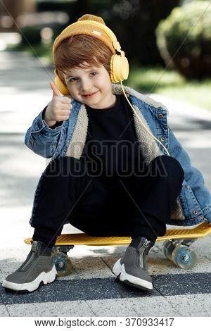 Portrait Of Cute Little Boy Sitting On The Skateboard Or Pennyboard Shoy Thumb Up In Street.
