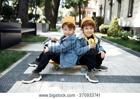 Two Gleeful Twin Boys Sitting On The Skateboard Or Pennyboard Looking Each Over Up In The Street.