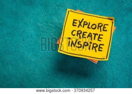 explore, create, inspire - inspirational reminder on a sticky note against blue textured paper background, personal development concept