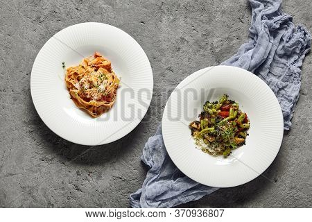Pappardelle pasta with salmon and sauce bisque served in white plate top view. Appetizing gemelli with vegetables. Traditional Italian dishes flat lay on grey surface with decorative tartan cloth