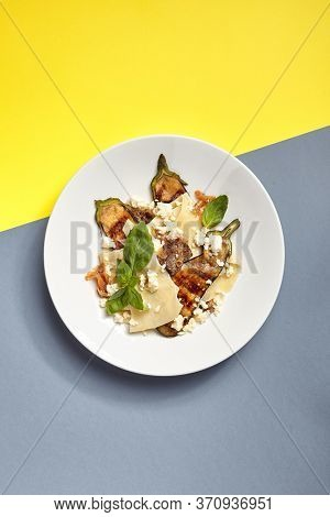 Lasagna with eggplant on white restaurant plate. Top view. Restaurant modern food concept.