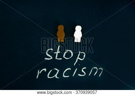 Black And White Figures Of People On A Black Background. The Inscription In Chalk-stop Racism. Black