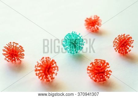 Red Coronavirus Balls Surrounded A Turquoise Ball On A White Flat Surface. Selective Focus On Turquo