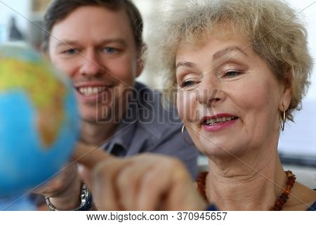 Close-up Of Senior Good-looking Woman And Middle-aged Man Explore Globe. Mother And Son Decide Where