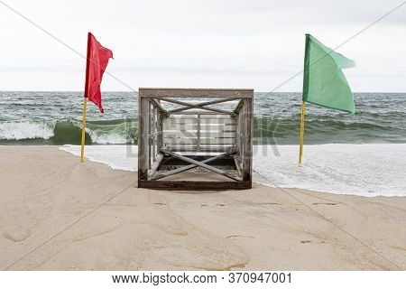 A Lifeguard Stand Lying On The Sand Ot The Beach With The Ocean Waves In Background And Red And Gree