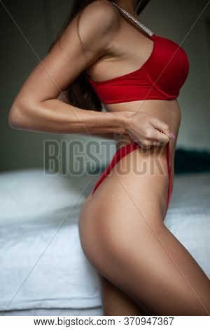 Beauty Woman In Red Lingerie. Attractive Fashion Model In The Bedroom.