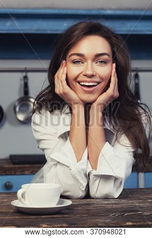 Happy Young Woman Drinking Tea On The Kitchen In The Morning. Wearing White Mans Shirt.