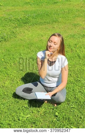 A Young Beautiful Girl In A White T-shirt With Her Eyes Closed Sits On The Green Grass On The Lawn W