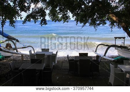 Empty Terrace With No Tourists And Jukung Boats On Sunny Day In Bali, Indonesia. Tables And Chairs A