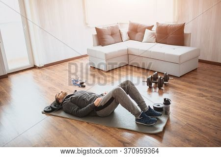 Young Ordinary Man Go In For Sport At Home. Regular Beginner Lying On Mat On Floor And Has Rest. Rea