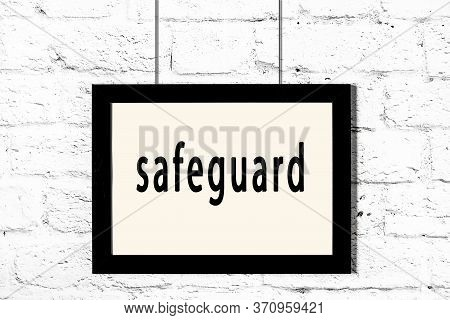 Black Wooden Frame With Inscription Safeguard Hanging On White Brick Wall