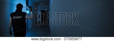 Security Guard At Night With Flashlight Inside Building
