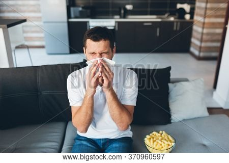 Young Man Watch Tv In His Own Apartment. Guy Sneezing Into White Napkin. Sick And Ill At Home. Suffe
