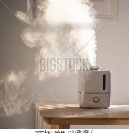 Close Up Of Aroma Oil Diffuser On The Table At Home, Steam From The Air Humidifier. Ultrasonic Techn