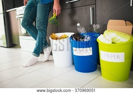 Close-up Concept. Sort Garbage At Home. There Are Three Buckets For Different Types Of Garbage. Guy