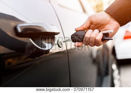 Close-up Of Car Keys. The Driver Opens And Closes The Auto. In The Residential Area Of The City