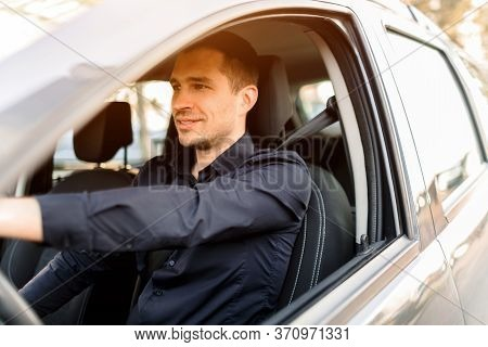 A Young Man In A Dark Shirt Driving His Own Car. Positive And Confident Taxi Driver