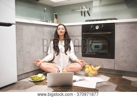 Beautiful Black-haired Woman Works From Home. A Female Model Sits On The Kitchen Floor In A Yoga Pos