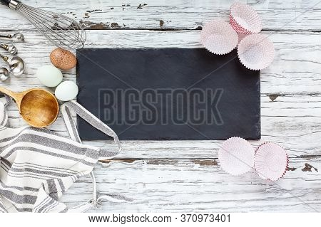 Blank Slate Sign With Cupcake Liners, Apron, Whisk, Measuring Spoons, Old Wooden Spoon And Eggs Over