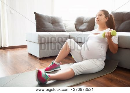Pregnant Woman Sitting On A Yoga Mat Holding Dumbbells In Her Hands. Workout And Sport For Pregnant