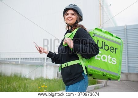 Kyiv, Ukraine - May 06, 2020: The Uber Eats Courier. The Food Delivery Woman Uses A Smartphone To Re