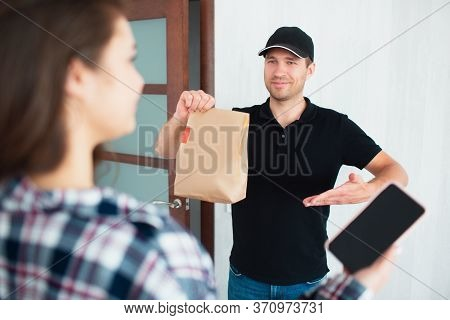 Food Delivery Concept. Food Delivery Man Brought Food Home To Young Woman. She Wants To Pay For The