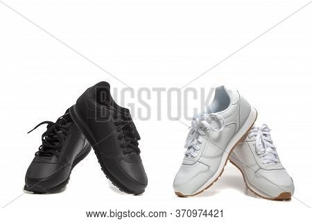 Black And White Concepts. Two Pairs Of New Black And White Modern Sport Trainer Shoes  Placed Over O