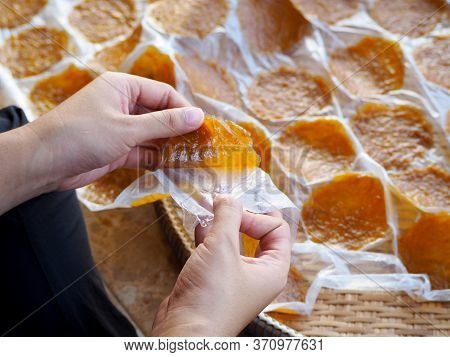 Hands Are Peeling Mango Sheets From Plastic Sheets.thai Dessert Mango Sheet.dried Mango Paste Made F