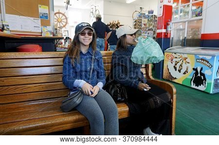 Mackinac Island, Michigan / United States - June 11, 2018: Passengers Sit In A Waiting Shelter To Aw