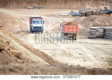 Two Multi-ton Heavy Mining Dump Trucks Empty And Loaded During Removal Of Construction Soil From Con