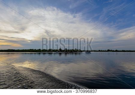 Wide View Of The Chobe River In Botswana As The Sun Begins To Set. A Small Boat Is Visible Just Pass