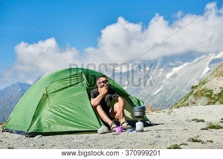 Man Tourist Sitting Inside Camp Tent And Using Walkie-talkie. Male Traveler With Radio In Hand Resti