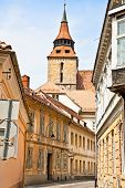 Narrow downtown street with Black Church ( Biserica neagra) in Brasov, Transylvania, Romania. poster