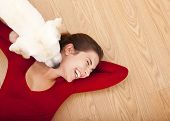 Woman lying on the floor and her dog licking her face poster