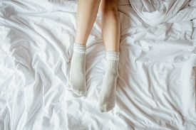 Slim And Charming Crossed Woman Legs On Bed. Cropped Image Of Erotically Lying On Bed. Conceptual Of