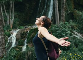 Beautiful Woman Smiling In Nature. Happy People Lifestyle. Woman In Front Of Waterfall. Nature Lifes