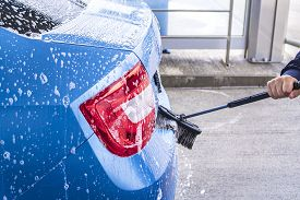 Man Washing His Car In A Self-service Car Wash Station.a Man Washes A Car On His Own. Car Wash Self-
