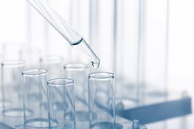 Pipette With A Drop And Scientific Laboratory Test Tubes In A Research Laboratory.