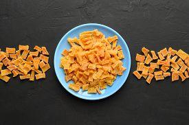 Dried Pumpkin Slices In Plate On A Dark Stone Background. Candied Pumpkin. Top View.