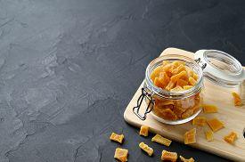 Dried Pumpkin Slices In Jar On A Dark Stone Background. Candied Pumpkin. Copy Space