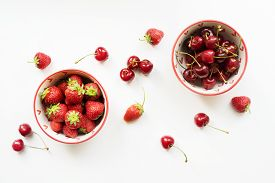 Two Red Bowls With Strawberries And Cherries With Scattered Berries On A White Table.