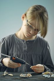 A Blonde Girl With Glasses Is Engaged In Creative Work With Glue Gun.