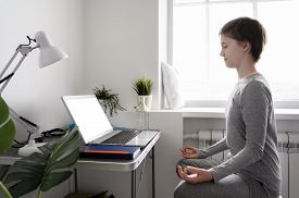 Teenager Girl Is Training At Home, Doing Yoga Exercises, Sitting In Lotus Position, Meditation. Sits