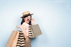 Happy Young Asian Woman Shopping Trendy Clothes On Blue Background