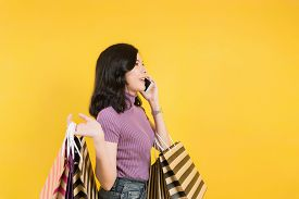 Happy Young Asian Woman Shopping Trendy Clothes On Yellow Background