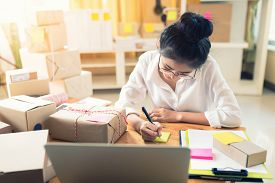 Asian Woman Working On Laptop At Home Are Arrange Delivery Packaging