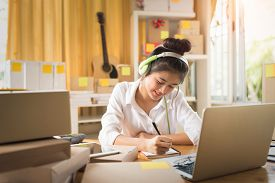 Asian Woman Working On Laptop At Home Are Arrange Delivery Packaging For Customers.