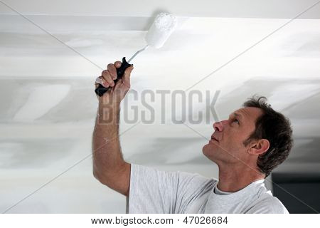 Man painting his ceiling white